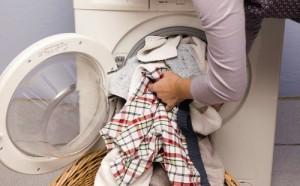Frau-steckt-Waesche-in-Waschmaschine_GreatImageInGallery